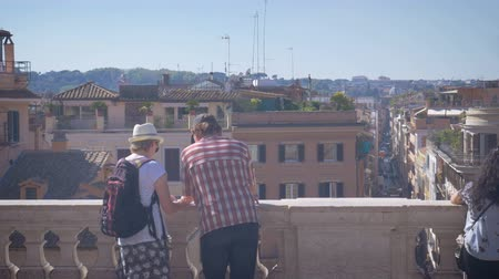 a couple of tourists looking on a map, the city panorama of Rome Stock mozgókép
