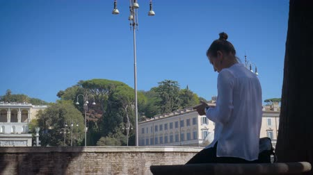 girl uses a smartphone on Piata di Popolo in sunny Rome