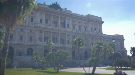 corte : Supreme court, piazza cavour in Rome on a sunny day, paradise palms on the square near the Italian flag Stock Footage