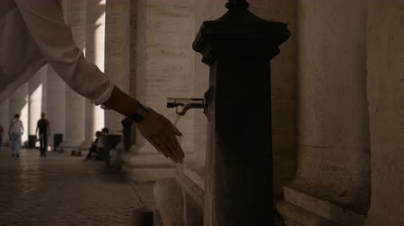 girl washes hands at Vatican at the fontanella close-up Stock mozgókép