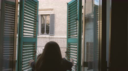 Female opens shutters of old window looking to the street of old Italian town Stock mozgókép