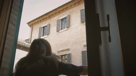 Female opens shutters of old window looking the street old Italian town Stock mozgókép