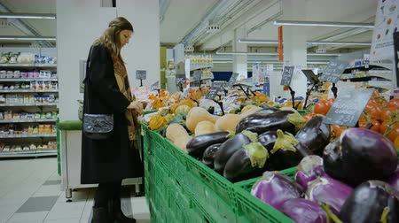 A girl chooses the vegetables in the supermarket in Italy Stock mozgókép