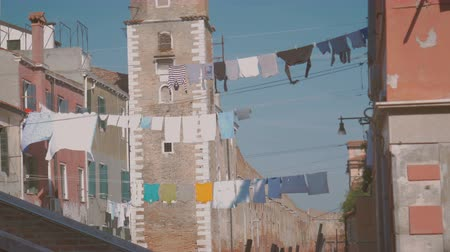 белье : Linen is dried on a rope in the middle of the street on a sunny day in Venice