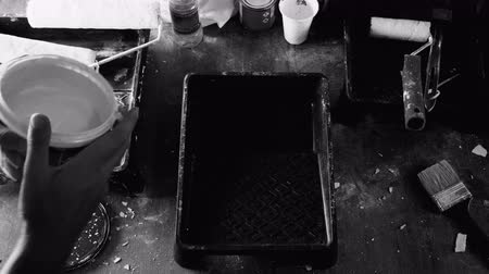 Close up male pouring white paint into the black tray, lack and white shot top view16mm style