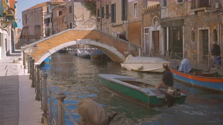 Boat floating near the bridge Venice people walk along the water Italy sunny day