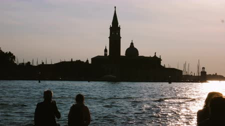 Silhouettes of People sitting enjoying sunset in Venice on the canal, male photographs the landscape