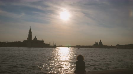 silhouette of a girl sitting enjoying sunset in Venice on canal Stock mozgókép