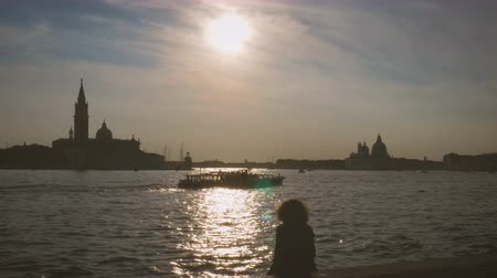 silhouette of girl sitting enjoying sunset in Venice on canal with floating boats