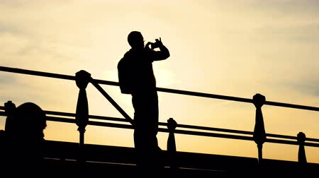 silhouette of a man photographing a sunset on a pedestrian bridge Venice Stock mozgókép