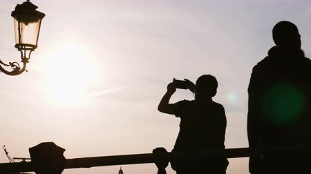The silhouette of a man photographing a sunset on the pedestrian bridge