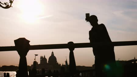 contornos : Silhouette of a person making selfie at sunset on the pedestrian bridge Venice