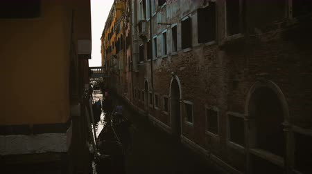 The gondolas floating through a narrow channel in Venice in the evening Stock mozgókép