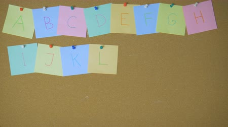 rajzszeg : Alphabet from A to Z. Hands pining sticky notes on pin board funny animation