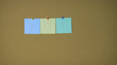 kandidát : Vote. Hands pining sticky notes on pin board funny animation