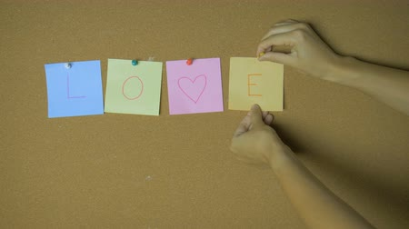 Love. Hands pining sticky notes on pin board funny animation Stok Video