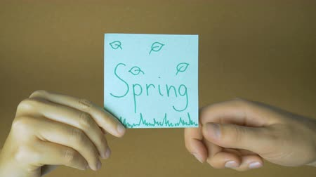 rajzszeg : Seasons in motion. Hands passing each other sticky notes with letters funny animation