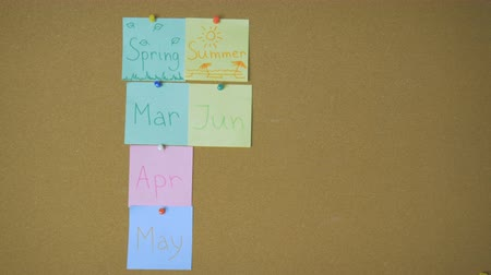 haziran : Calendar. Hands pining sticky notes with months and seasons on pin board funny animation Stok Video