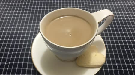 vaření v páře : Cinemagraph - Steaming white cup of coffee with heart shaped cookie on a table with a checkered tablecloth