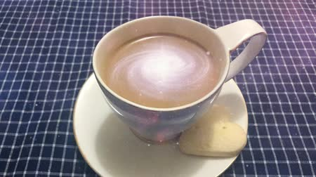 masa örtüsü : Cinemagraph - Galaxy in the cup of coffee. Steaming white cup of coffee with rotating galaxy in it on a table with a checkered tablecloth Stok Video