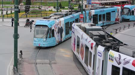 trilho : Istanbul, Turkey - April 20, 2013: A street tram approaches to Eminonu Station while a second one departs at the same time.