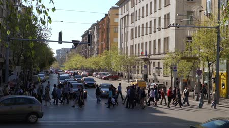 bulgaristan : Sofia, Bulgaria – April 25, 2013: A crowd of pedestrians people crossing over Alexander Stamboliski Street and an electrical tram is passing through on a busy week day in Sofia, Bulgaria.