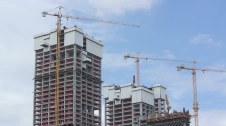 housing problems : A timelapse movie of a construction project with stopped cranes while the clouds moving over it. Combination of stills taken with a Nikon J1 camera on a tripod. Stock Footage