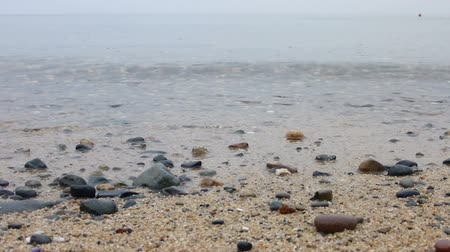 rainy : Low angle shot at the beach while it is raining on an overcast day. With ambient sound. Shot on a tripod.