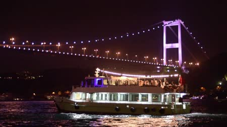 vyhlídkové : Fatih Sultan Mehmet Bridge over the Bosphorus Strait at night in Istanbul, Turkey. An excursion boat passes, fast forwarded.