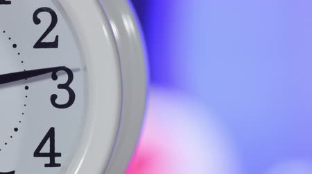 atık : Table clock close-up timelapse with a television set blurred at the background