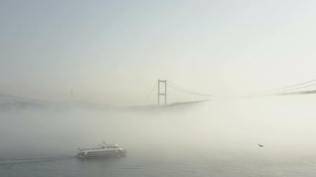 fogged : Bosphorus view on a foggy day in Istanbul, Turkey. The fog creates an unusual mystical ambiance with the Bosphorus Bridge at the background a boat in the foreground. Stock Footage