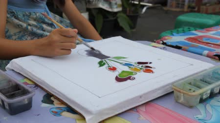 Child hand painting flower vase on a canvas painting.