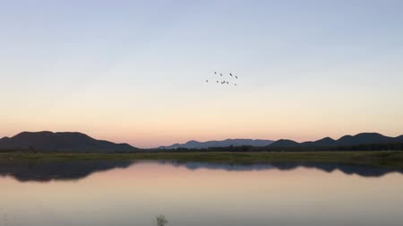 awesome : Sunset in twilight time behind the mountains front water of a reservoir.