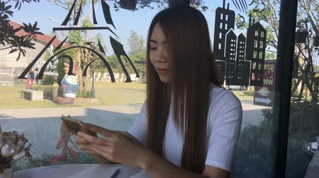 mensagens : Asia girl use smart phone emotion happy and smile in cafe. Vídeos