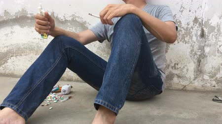 kokaina : Asian man smoking cigarette is sad and pain by drug addiction problem. World no tobacco day, 31 may.
