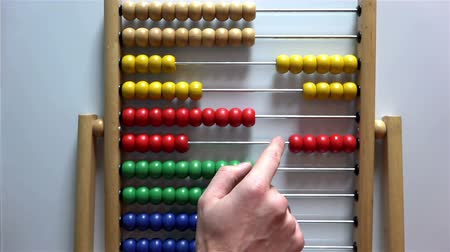 abacus : Mans hand moves the bones in the accounts of an abacus on white background