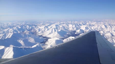 virginity : Flying an airplane during the day over the white snow-capped mountains and Stock Footage