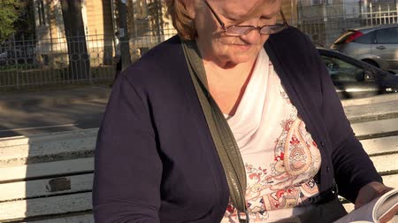 starość : grandmother wrinkles on the face and glasses carefully read the books sitting on the bench