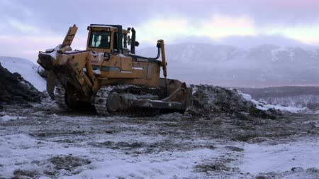 bagger : Bystrinsky District Kamchatka Krai district center village Milkovo 9 December, 2015 Bulldozer working on the top of huge pile of marble pebble on Thassos in Greece