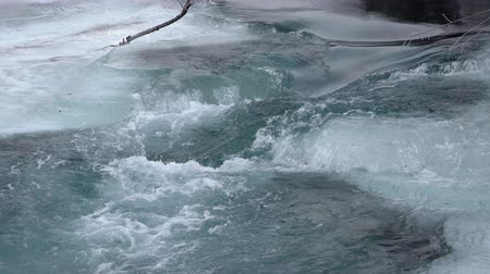 sobre o branco : icy dark blue water licks blocks of ice flowing down the river