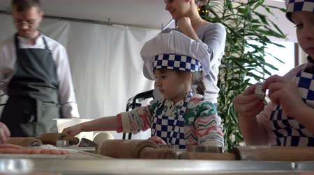 repast : RUSSIA, St. Petersburg, January 10, 2016: young cook in the special form of blue white color learn to cook different sweets with adult parents, St. Petersburg