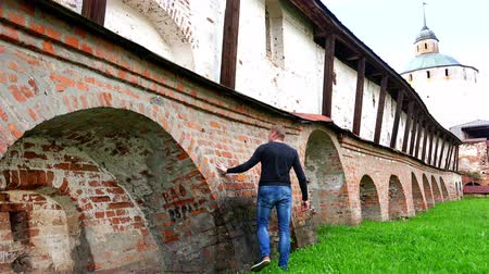 touched : RUSSIA, town Kirillov, Cyril-Belozersky Monastery, July 8, 2016: Tourist touches the historical reference massive brick walls of the monastery guarding against enemies Stock Footage