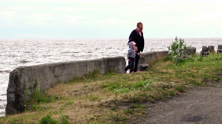 farag : RUSSIA, city Lipin Bor, July 8, 2016: Mom with a child hiding from the cold and strong wind on the dock by the lake and go with a walk