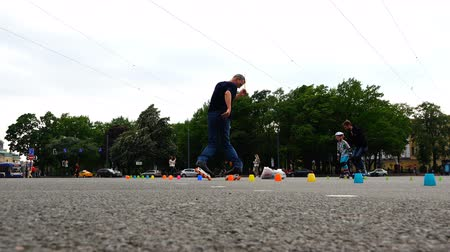 slalom : athletes on roller skates and uniforms ride on the pavement with obstacles