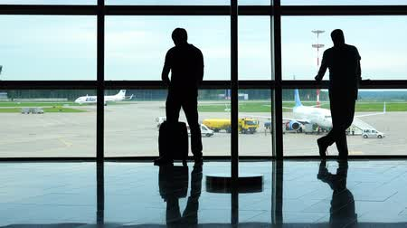 taking flight : two passengers watching the aircraft traffic through the airport window Stock Footage