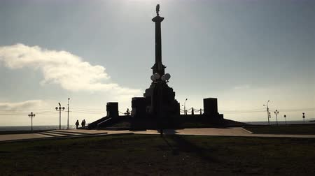 citylandscape : the outline of the urban monument with the arms of Russia on a pillar shape and visitors