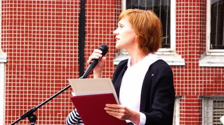 speach : a woman with a microphone and a folder in her hand broadcasts text on a piece of paper Stock Footage