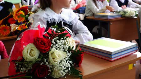 schoolbook : Flowers and textbooks on school desk schoolgirls in first grade on the day of knowledge