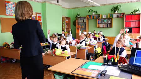schoolbook : Children in the class pull their hands up answering the teachers questions