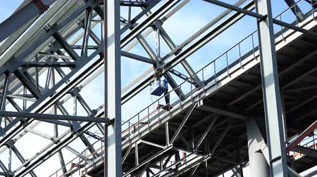 laboring : Welder in a mechanical hoist on a platform at a height produces welding work